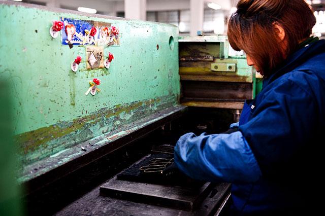 Diese sogenannten Cutting Molds werden von einer Arbeiterin routiniert auf einen Stoffstapel gelegt und in eine Maschine geschoben, welche die Metallform dann in den Stoff hineindrückt und diesen so zurechtschneidet. Wie fast überall in der Handschuhproduktion ist auch hier akkurates Arbeiten oberste Priorität. Die Molds müssen so angeordnet werden, dass der Stoff optimal ausgenutzt wird und möglichst wenig Ausschussmaterial entsteht. Bei den abertausenden Gloves, welche die Fabrik jedes Jahr in alle Welt verlassen, zählt jeder Quadratzentimeter Stoff, der nicht verschwendet wird.