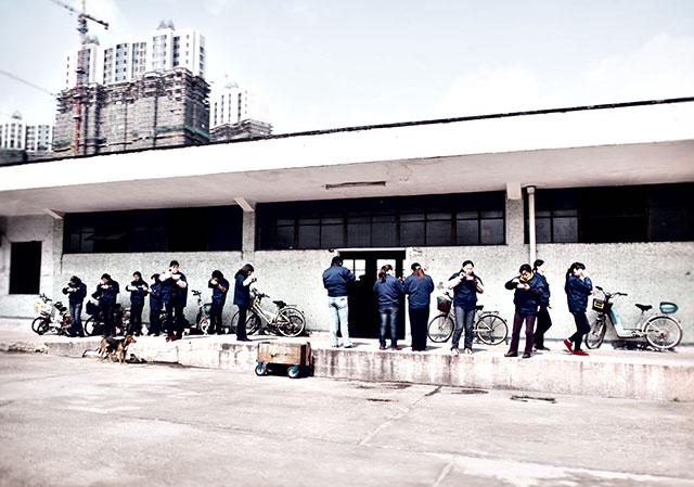 """Ausgelassen miteinander tratschend laufen die Näherinnen an mir vorbei zur firmeneigenen Essensausgabe vor der Fabrik. """"Das wäre vor 30 Jahren noch nicht denkbar gewesen"""", fügt Shin zufrieden über die enorm verbesserten Arbeitsbedingungen an. Vor der Fabrik stehend schlürfen die chinesischen Arbeiterinnen ihre wohlverdiente Nudelsuppe. Im Hintergrund sieht man Kräne, welche einen mit Baugerüsten umhüllten Wolkenkratzer aus dem Boden stampfen. Sinnbild für ein Land im Aufbruch."""